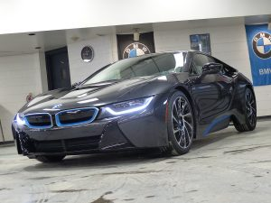 Black BMW with lights on
